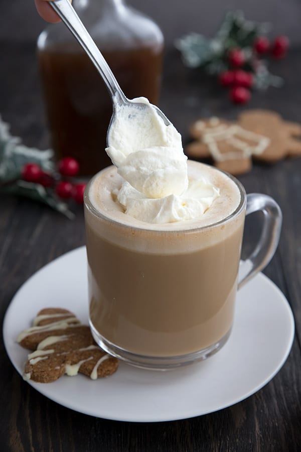 Spooning some keto whipped cream onto a sugar free gingerbread latte