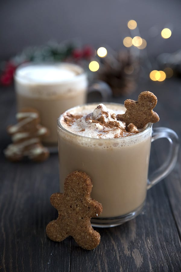 Two gingerbread lattes on a wooden table, with gingerbread men and Christmas lights.