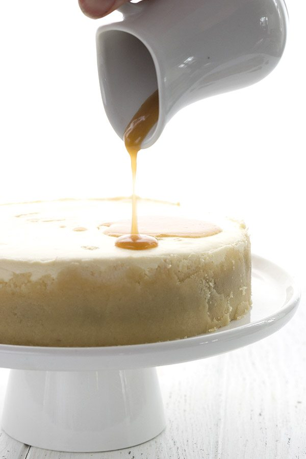 Sugar-free caramel sauce pouring over low carb instant pot cheesecake