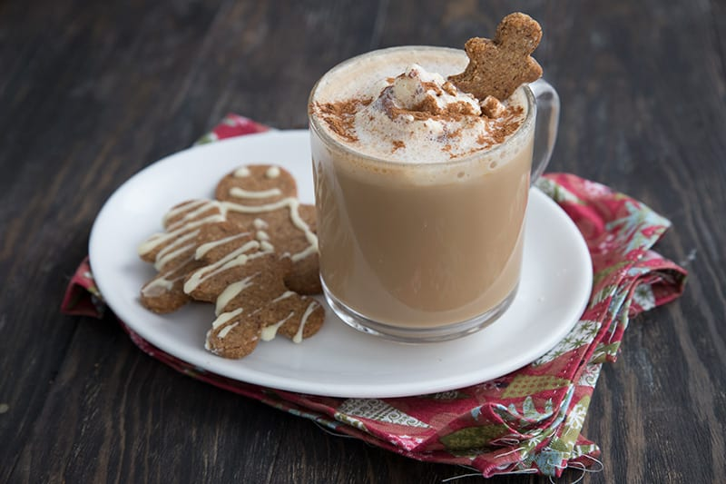 A gingerbread latte in a clear mug sits on a white plate with two keto gingerbread cookies.