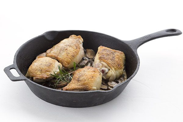 Chicken thighs in a cast iron pan with mushrooms.