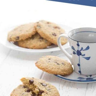 Chewy low carb chocolate chip cookies on a white table with a cup of coffee