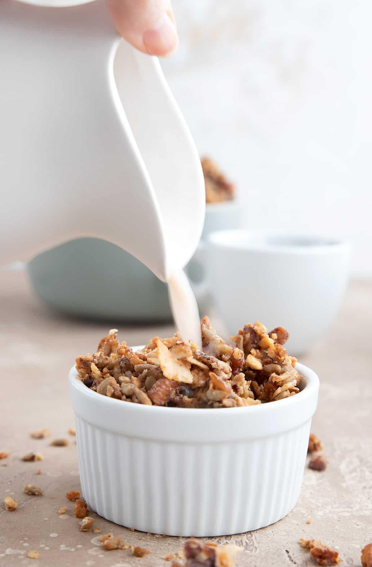 A white jug pours almond milk into a bowl of low carb granola