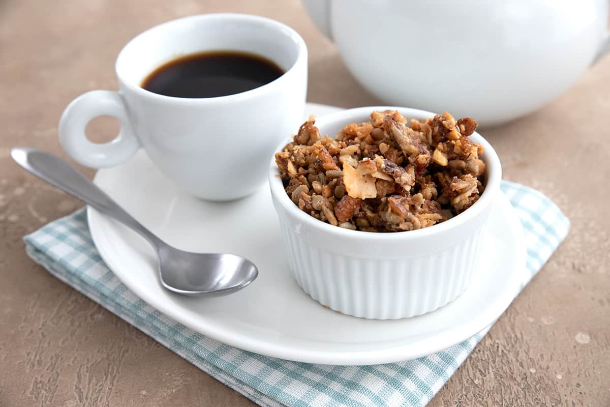 A small bowl of peanut butter granola on a white plate with a cup of coffee.