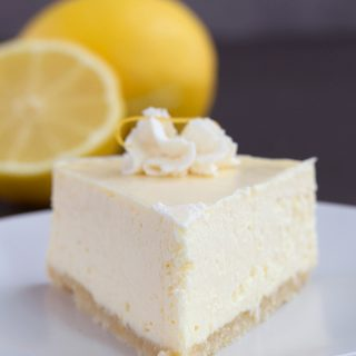 Keto Instant Pot Lemon Cheesecake on a white plate with cut lemons