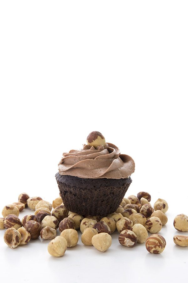 Keto Chocolate Cupcakes with Hazelnut Frosting on a pile of hazelnuts