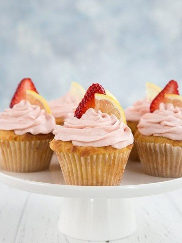 Keto Strawberry Lemonade Cupcakes - low carb lemon cupcakes with creamy sugar-free strawberry frosting. Topped with a slice of lemon and strawberry.