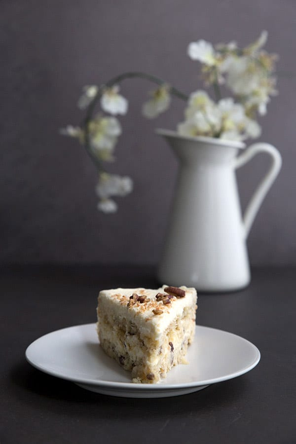 A slice of sugar-free and gluten-free Italian Cream Cake with a vase of flowers behind.