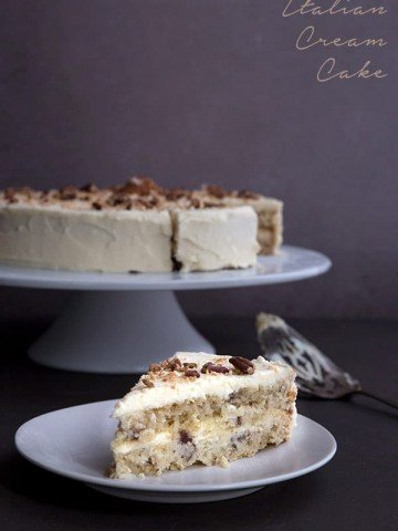 Keto Italian Cream Cake Recipe - a slice of cake on a white plate with the large cake in behind.