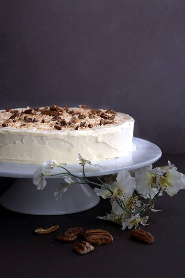 Low Carb Italian Cream Cake on a white cake stand with flowers