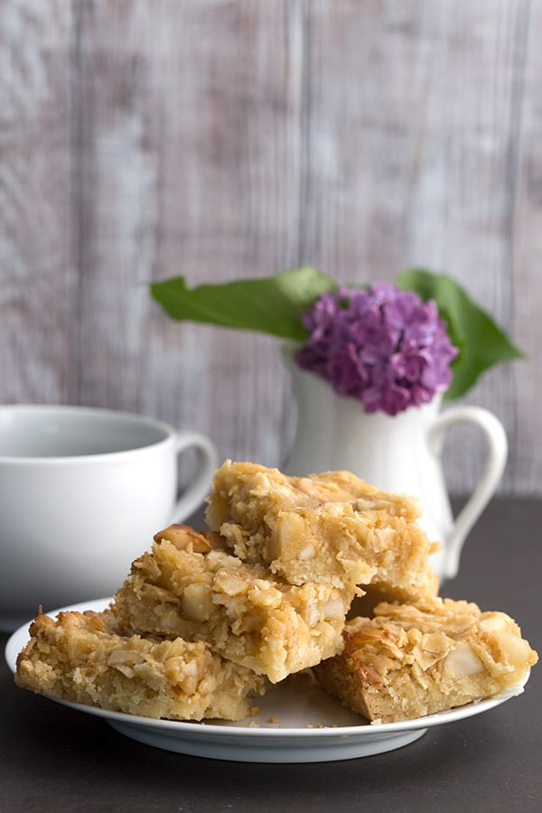 Coconut Macadamia Bars on a white plate with lilacs in behind