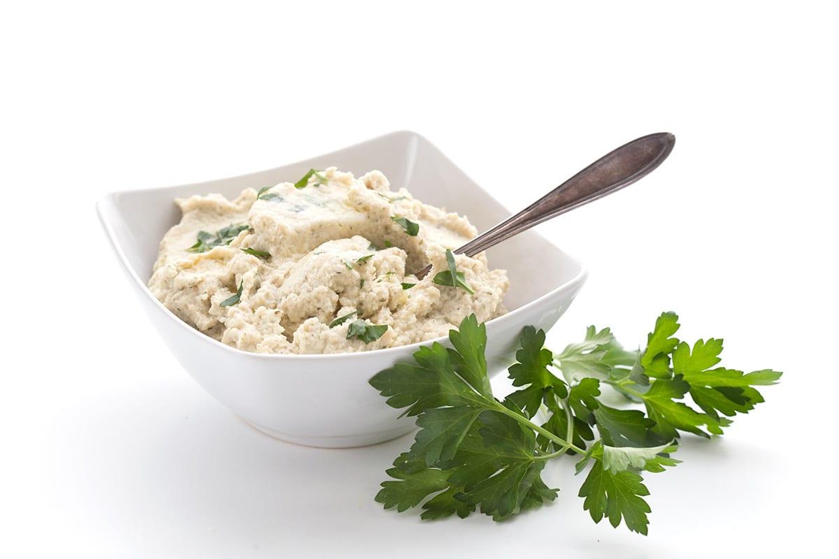 Keto cauliflower mash in a white bowl with a spoon.
