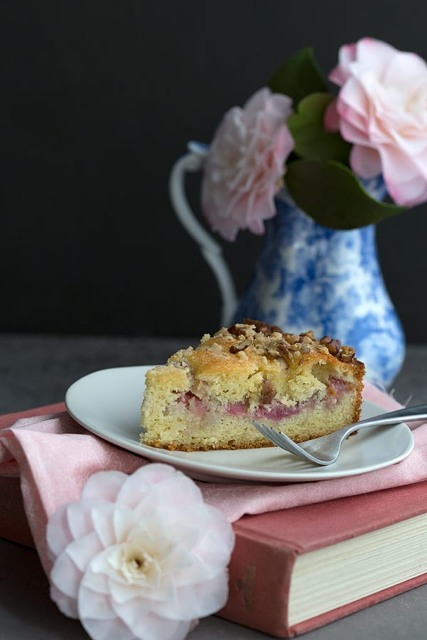 A slice of low carb coffee cake on a book with flowers in the background