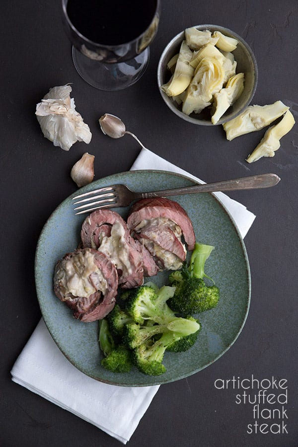 Keto artichoke stuffed flank steak on a plate with broccoli, along with a glass of wine.
