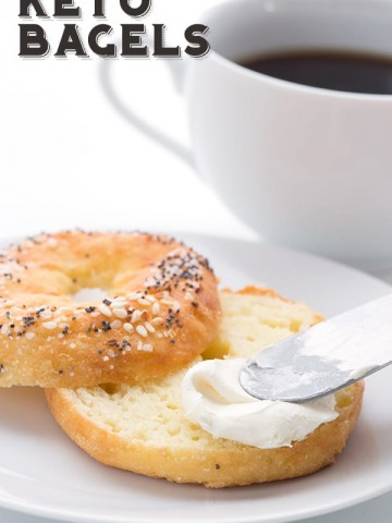 Keto everything bagels on a white plate being smeared with cream cheese.