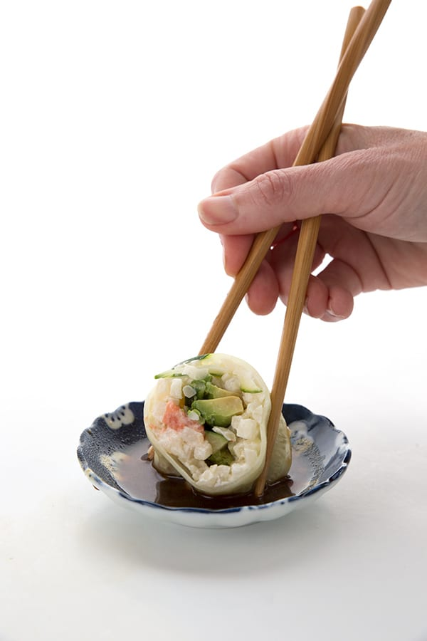 Dipping a piece of keto California Roll into soy sauce
