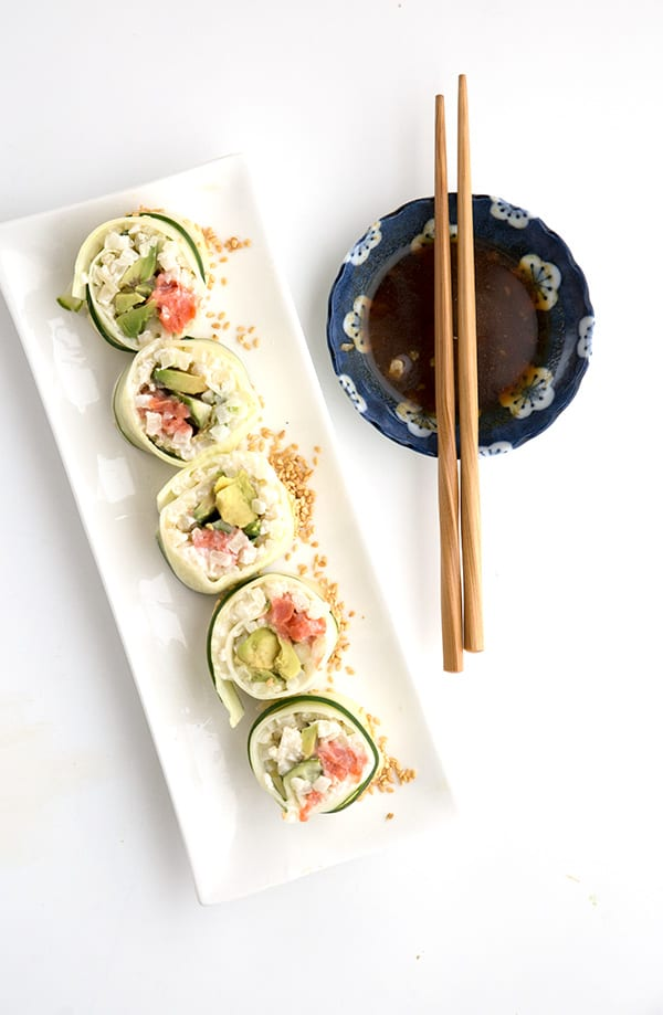 Top down photo of low carb California Roll on a white plate with a bowl of soy sauce and chopsticks