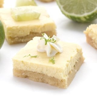 Keto Key Lime Bars with limes and whipped cream. Sugar-free.