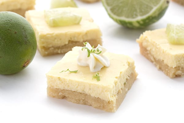 Keto Key Lime Bars close up with limes and whipped cream. Sugar-free.