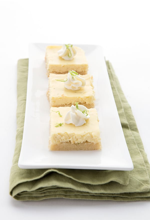 Low Carb Key Lime Pie Bars in a row on a white plate with a green napkin underneath