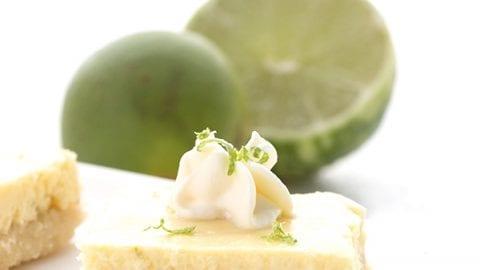 Sugar-free key lime bars with limes behind.