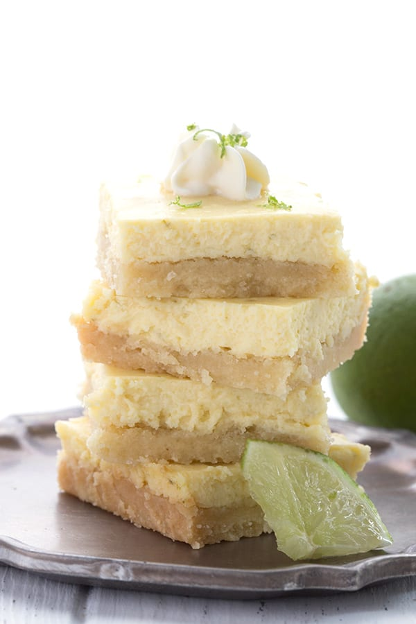 A stack of key lime bars on a pewter plate with a dollop of whipped cream on top.
