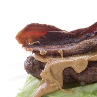 Burger topped with peanut butter and bacon on a lettuce bun