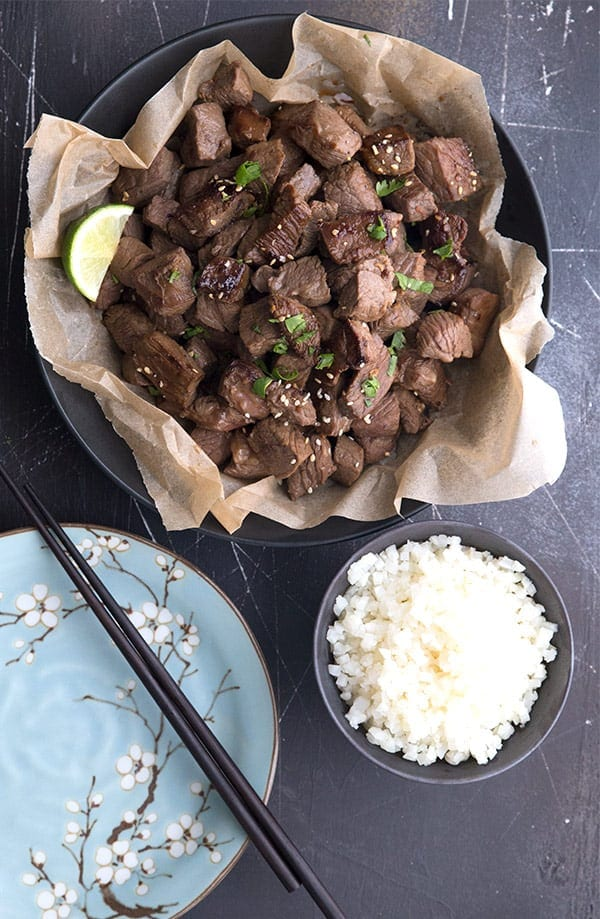 Asian steak bites in a bowl with cauliflower rice, a plate and chopsticks