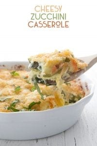 Low Carb Zucchini Casserole in a pan with a scoopful on a wooden spoon