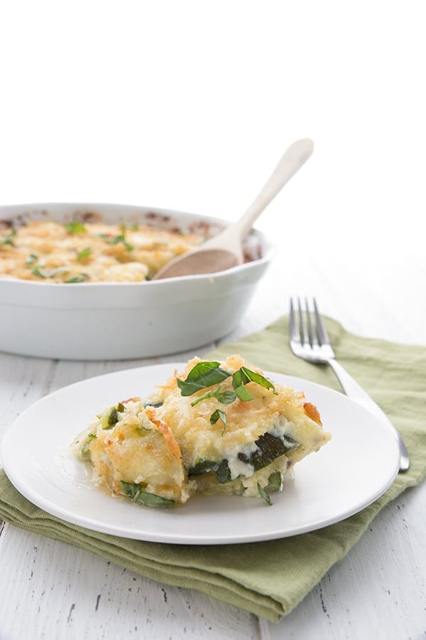 A serving of cheesy zucchini casserole on a plate with the large dish of casserole behind