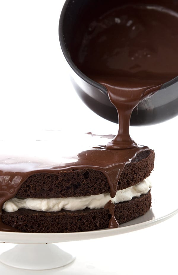 Sugar-Free chocolate ganache being poured over a chocolate layer cake with a cream filling