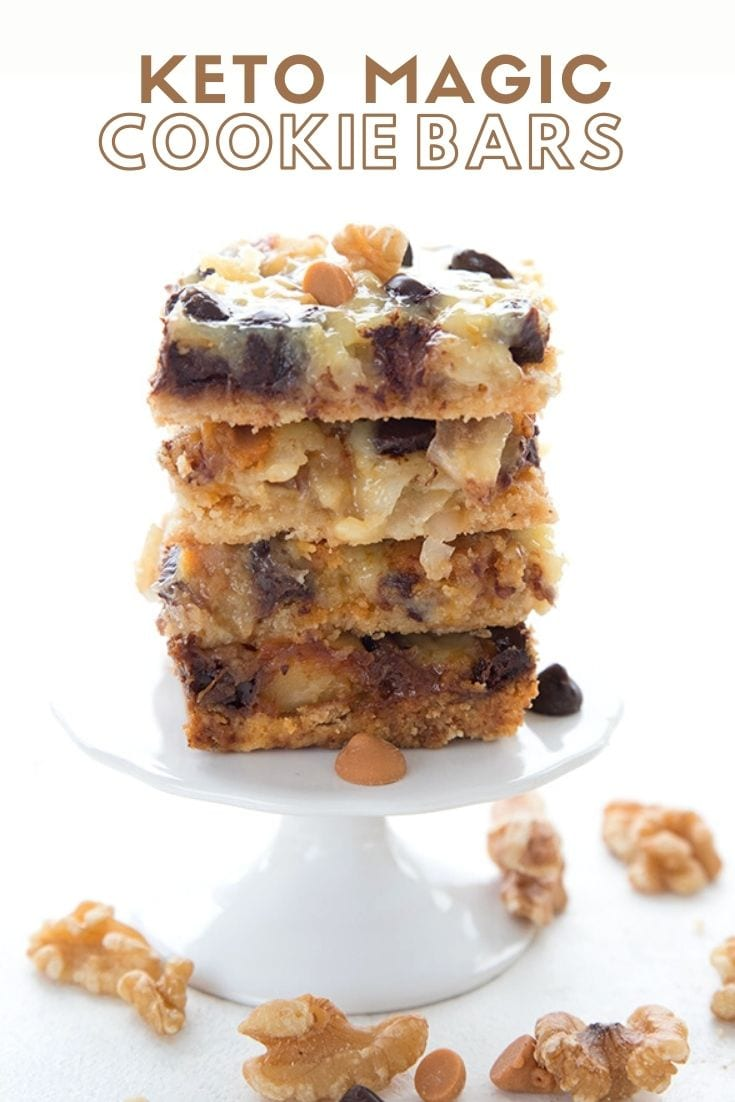 A stack of keto magic cookie bars on a white cupcakes stand, with nuts and butterscotch chips strewn around.