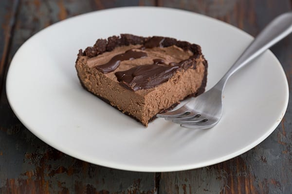 A slice of mini no-bake chocolate cheesecake on a white plate with a fork