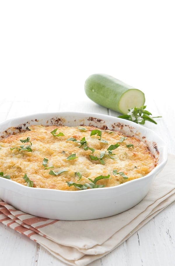 Baked zucchini casserole in a white pie dish with zucchini in the background