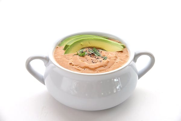 Tomato bisque in a white bowl with avocado slices on top