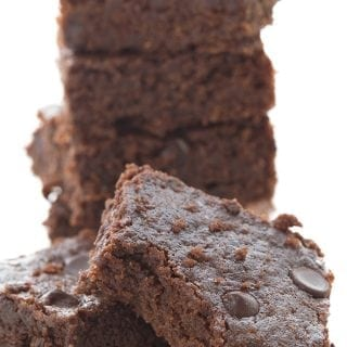 A stack of easy keto brownies. One in front has a bite taken out of it.