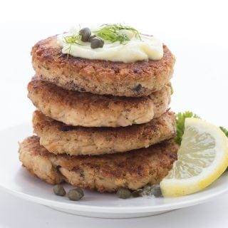 Lemon Dill Tuna Patties in a stack with mayo, capers, and dill