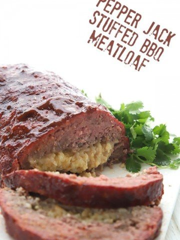 Smoked meatloaf stuffed with Pepper Jack Cheese on a white plate with parsley