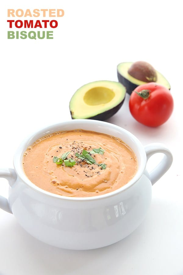 Dairy Free Low Carb Roasted Tomato Bisque in a white bowl with a tomato and avocado in the background