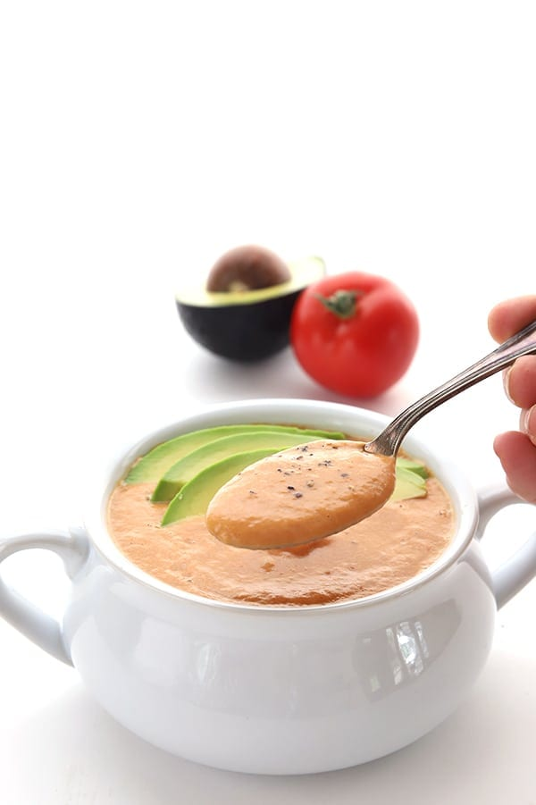 A spoonful of roasted tomato soup above a bowl full of the soup