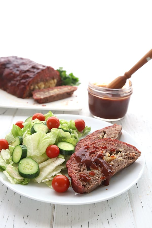 Slices of stuffed meatloaf on a plate with salad