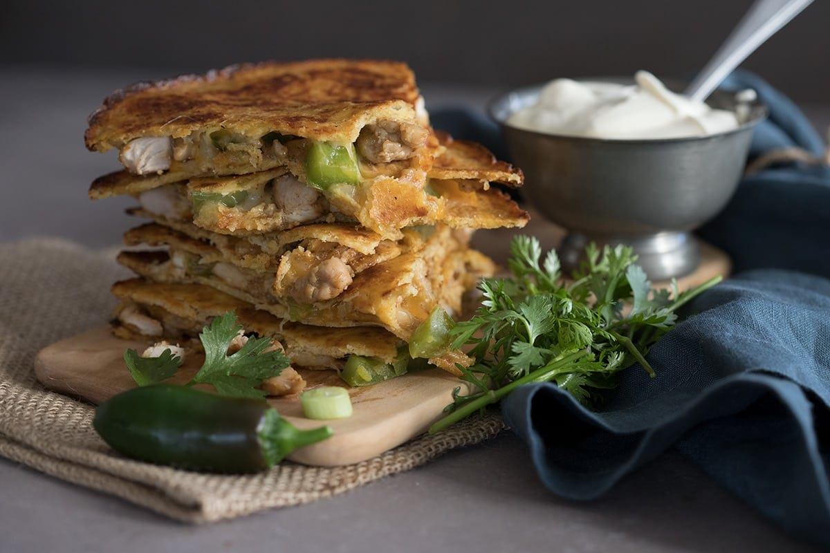 A stack of low carb chicken quesadillas with a bowl of sour cream behind