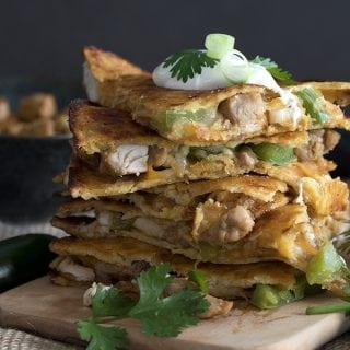 Easy Keto Chicken Quesadillas in a stack on a cutting board with sour cream on top.