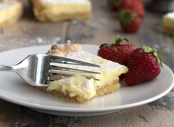 A fork going into a piece of keto gooey butter cake on a white plate