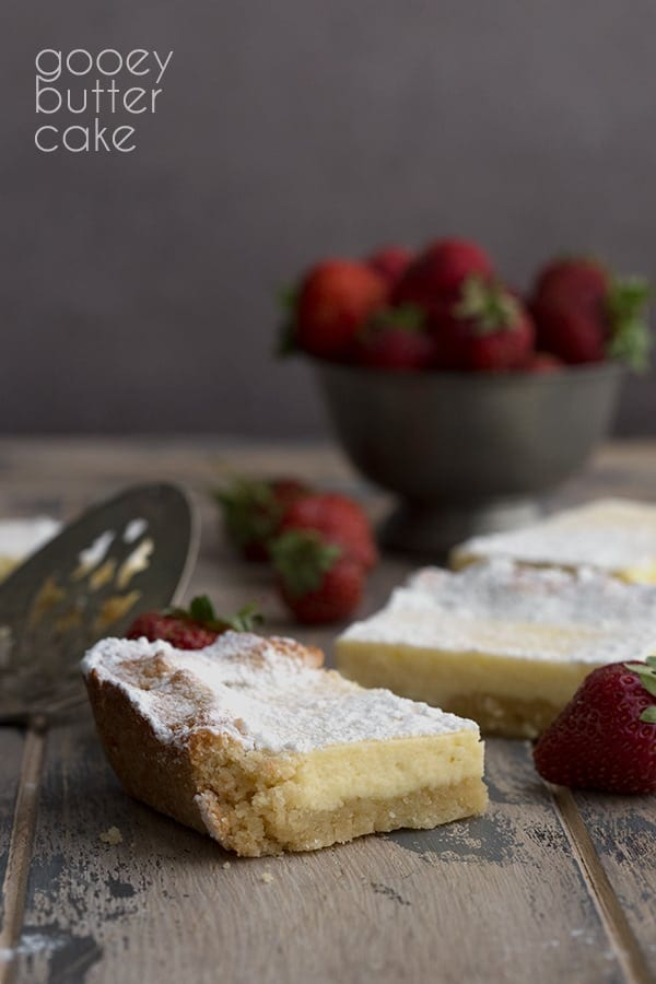 Keto Gooey Butter Cake slice on a wooden table with strawberries in the background