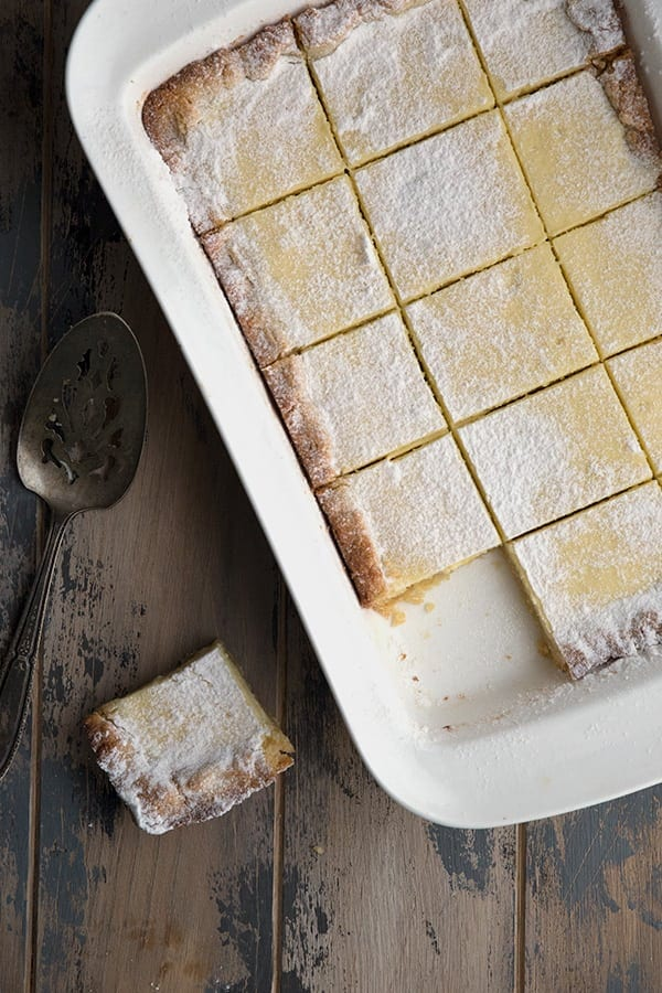 Easy St Louis Gooey Butter Cake in a pan with one piece cut out