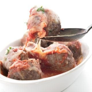 Meatball parmesan in a white oval dish with a spoon lifting one meatball away from the rest.