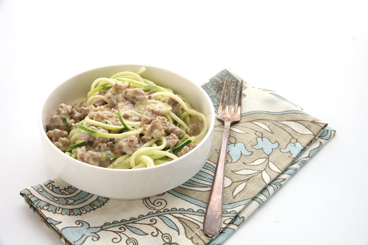 Keto alfredo sauce with zoodles and sausage in a white bowl. A napkin and fork nearby.