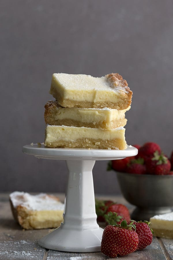 Pieces of keto gooey butter cake on a stack on a white cake stand
