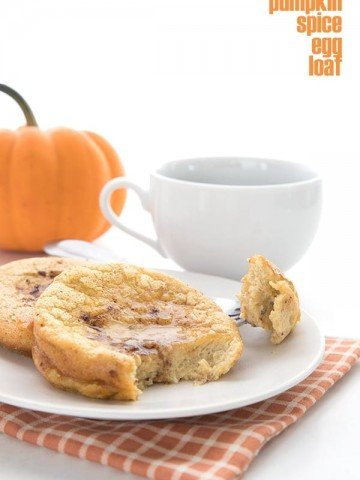 Pumpkin Spice Egg Loaf on a white plate with a cup of coffee and a small pumpkin in the background